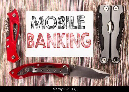 Conceptual hand writing text caption inspiration showing Mobile Banking. Business concept for Internet Banking e-bank Written on sticky note wooden background with pocket knife - Stock Photo