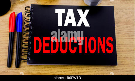 Conceptual hand writing text caption showing Tax Deductions. Business concept for Finance Incoming Tax Money Deduction written on sticky note with space on old wood wooden background with sunglasses - Stock Photo