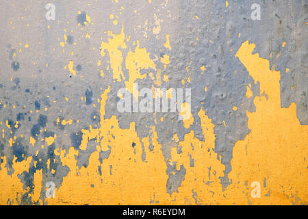 Wall in bad condition with old yellow and blue paint inside house in process of repair as background closeup - Stock Photo