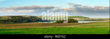 Picturesque panoramic view over Malham Tarn (glacial lake), limestone cliffs & pasture, under evening sky - Malhamdale, Yorkshire Dales, England, UK. - Stock Photo