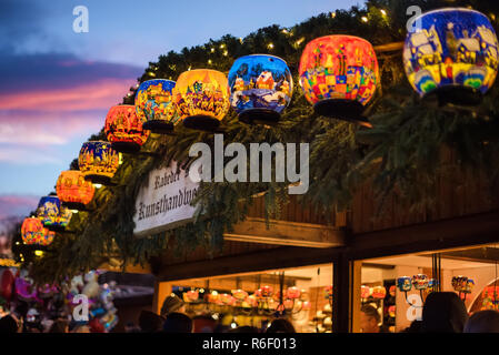 Vienna, Austria - December 24, 2017. Lighting painted glass candle holders with colorful ornaments in kiosk at Viennese Christmas market. Close view o - Stock Photo