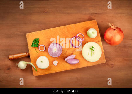 An overhead photo of various onion types on a wooden cutting board on a dark rustic background with a place for text. White, red, and yellow onions an - Stock Photo