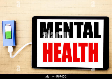 Handwriting Announcement text showing Mental Health. Business concept for Anxiety Illness Disorder Written on tablet with white background and charger power bank. - Stock Photo