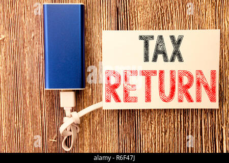 Conceptual hand writing text caption inspiration showing Tax Return. Business concept for Accounting Money Return written on sticky note old wood wooden background with power bank - Stock Photo