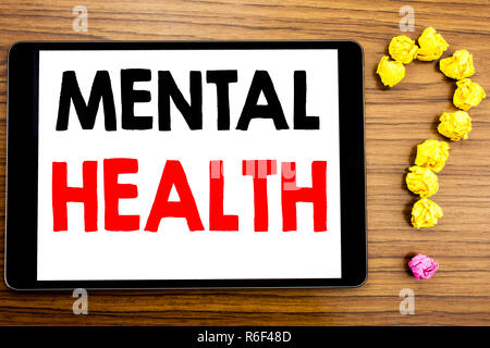 Writing text showing Mental Health. Business concept for Anxiety Illness Disorder written on tablet computer on the wooden background with question mark made of folded paper. - Stock Photo