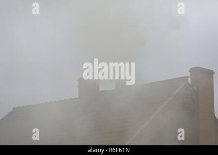 Smoke from the chimney of a house fueled with coal - Stock Photo