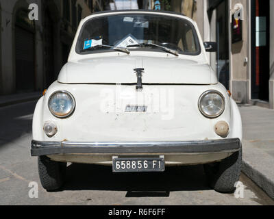 Horizontal close up of a dilapidated old Fiat 500 parked in Italy. - Stock Photo