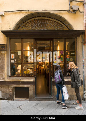Vertical view of tourists looking in a shop window in Lucca, Tuscany. - Stock Photo