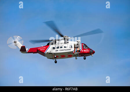 Horizontal close up of a coastguard helicopter in flight. - Stock Photo