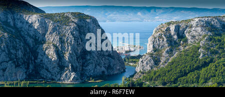 View to Omis from the mountains with the river Cetina, the town, the adriatic sea and in the background the island of Brac with a clear blue sky. - Stock Photo