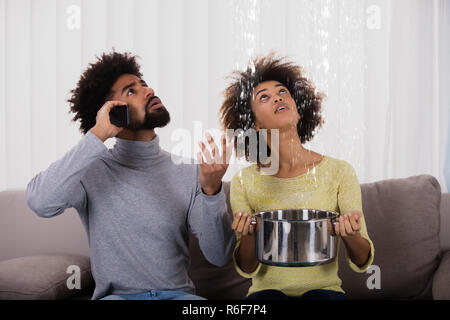 Woman Using Utensil For Collecting Water Leaking From Ceiling - Stock Photo