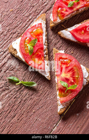 Four toast of rye bread with tomatoes and basil lie on a brown wooden board - Stock Photo