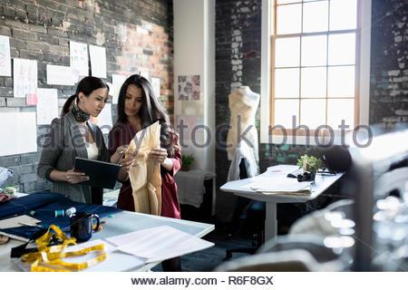 Female fashion designers working in loft office - Stock Photo