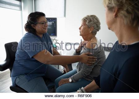 Female nurse examining shoulder of senior patient in clinic examination room - Stock Photo