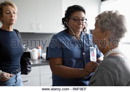 Nurse using stethoscope on senior woman in clinic examination room - Stock Photo