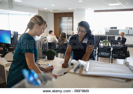 Female nurses discussing paperwork at clinic check-in counter - Stock Photo