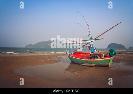 Wooden fishing boat on the coast of Thailand - Stock Photo