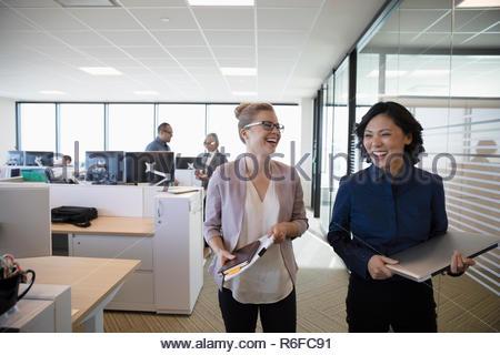 Laughing businesswomen walking in office - Stock Photo