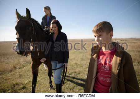 Mother and sons with horse in sunny field - Stock Photo