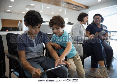 Boys using digital tablet while mother and nurse talk in clinic waiting room - Stock Photo
