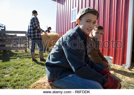 Portrait confident brothers sitting on hay bales on sunny farm - Stock Photo
