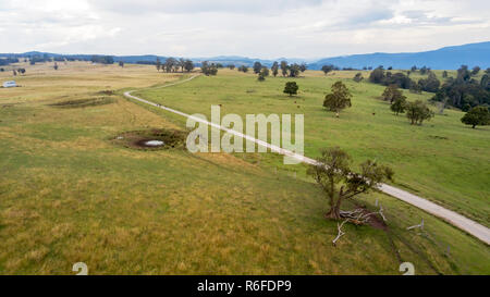 aerial view of country road running in the midst of green paddocks with mountains in the background - Stock Photo