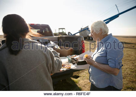 Senior female farmer eating lunch, taking a break on sunny farm - Stock Photo