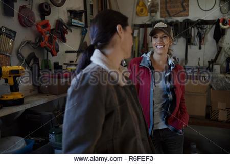 Female farmers talking in workshop - Stock Photo