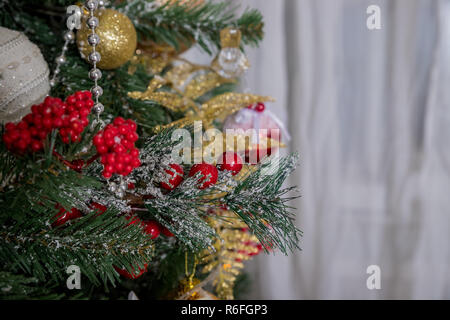 Christmas and New Year Decoration. Winter holidays art design with holiday baubles. Beautiful Christmas tree closeup decorated with gold star, holly berry, tinsel. Copyspace.baubles hanging from a decorated Christmas tree.Copy space - Stock Photo