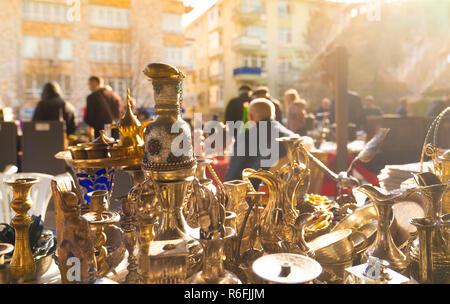 Various antique jars, jugs, pitchers at flea market with blurred customers and sellers in background, Ayranci Antika Pazari, Ankara, Turkey - Stock Photo