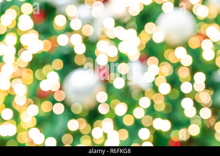 Blurred red, green, and gold bokeh background of Christmas tree. Xmas background. Christmas and Happy New Year holiday background. Beautiful bokeh bac - Stock Photo