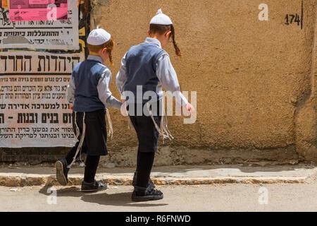 Ultra Orthodox Jewish Boys Walking On The Street In Mea Shearim Jewish Orthodox Quarter, Israel Jerusalem - Stock Photo