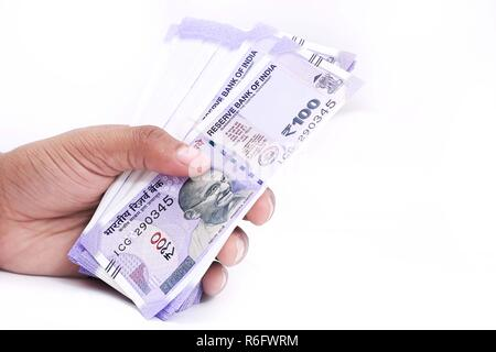 Picture of hand with new Indian currency notes. Isolated on the white background. - Stock Photo