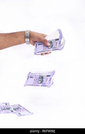 Picture of hand is throwing new Indian currency. Isolated on the white background. - Stock Photo