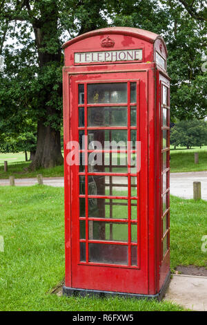 Old red telephone box surrounded by grass and trees at Wollaton Park, Nottingham, UK - Stock Photo