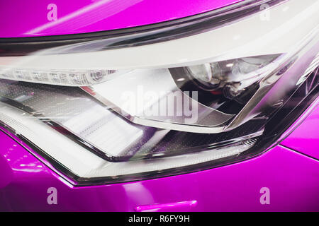 Close up shot headlight in luxury pink car background. Modern and expensive sport car concept - Stock Photo