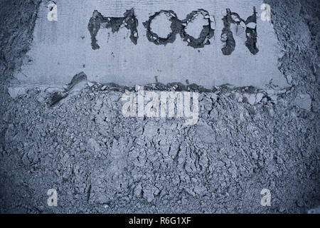 On gray moon sand is inscribed by moon. Copy space. On right is plant germ. Extraction minerals on moon. Colonization. Life on moon - Stock Photo