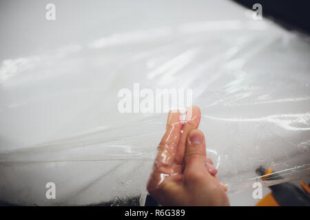 Transparent film, car paint protection, wrapping specialis. Car detailing. Selective focus. - Stock Photo