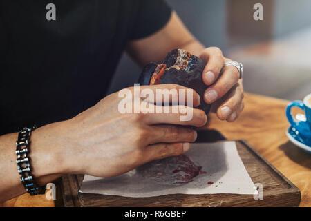 Close up of man hands holding black fresh juicy burger at cafe. - Stock Photo