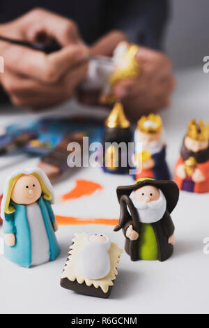 a caucasian man painting different handmade figurines of a nativity scene - Stock Photo