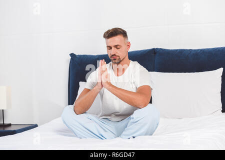 Handsome man practising yoga on bed - Stock Photo