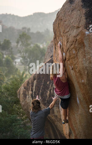 A male rock climber practices his skills, grip and strength