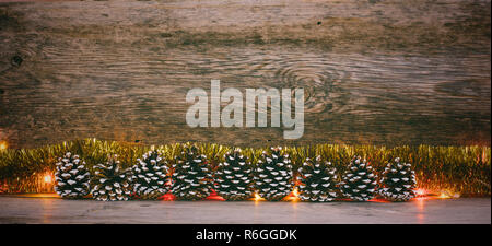 old wooden background with fir cones, gold tinsel and garland with space for text. the concept of new year Christmas. tinted photo - Stock Photo