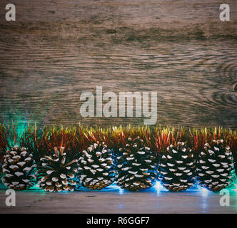 New Year's background. Fir cones, red tinsel and lights garland on a old barn boards. Tinted photo - Stock Photo
