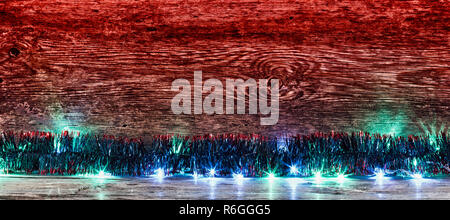 red old wooden background with blue tinsel and garland with space for text. the concept of new year Christmas. tinted photo - Stock Photo