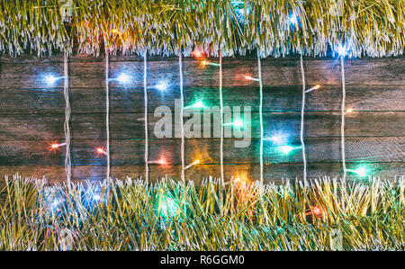 festive wooden background from old boards with colorful garland and gold tinsel. with space for text. the concept of a new year, Christmas. tinted pho - Stock Photo