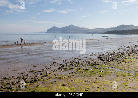 A family walking the tide line at Morfa Nefyn beach on the Llyn Peninsula in Wales - Stock Photo