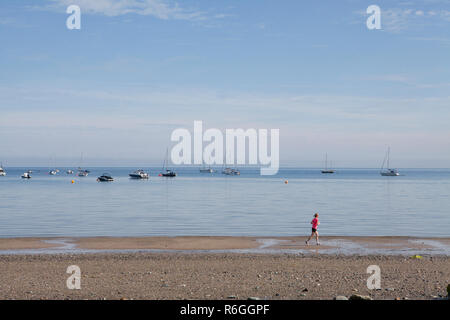A woman runs along an empty beach in front of moored boats on the Llyn Peninsula in Wales - Stock Photo