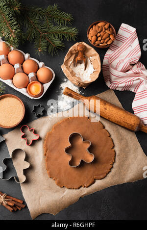 Gingerbread cookies preparation. Cookie dough, cookie cutters, ingredients on black background. Top view - Stock Photo