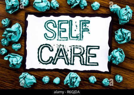Handwriting Announcement text showing Self Care. Business concept for Taking caring for own Health Written on sticky note paper, wooden background with folded blue paper meaning thinking - Stock Photo